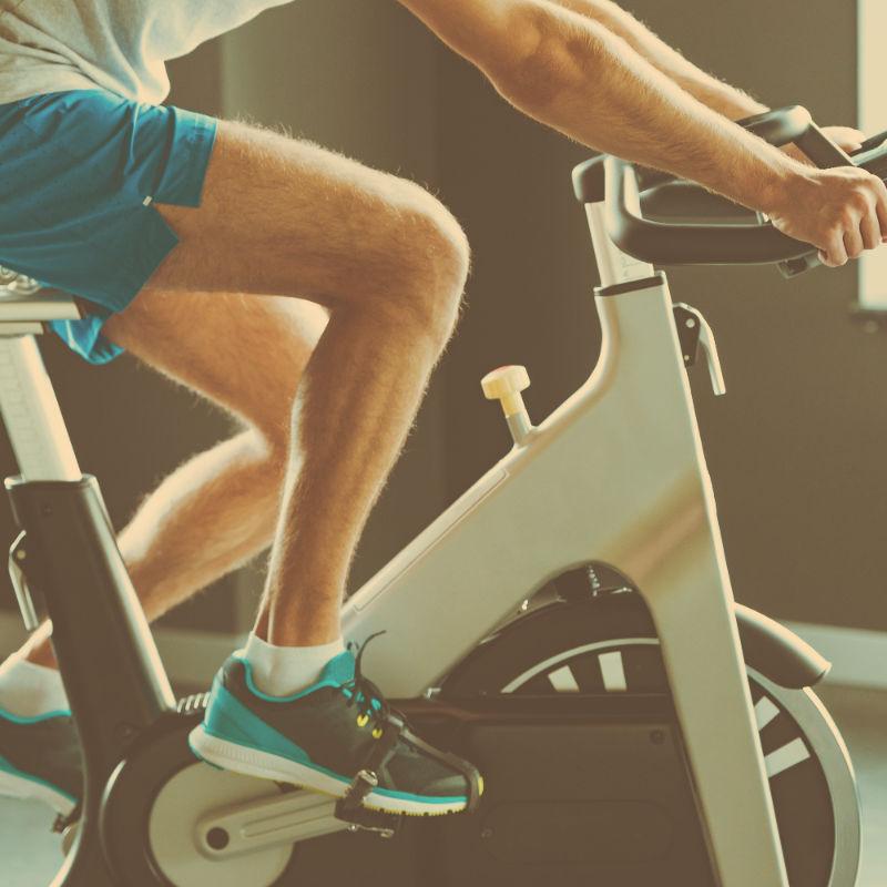 Man som cyklar på en träningscykel